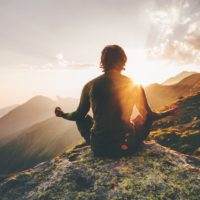 Man meditating at sunset in the mountains
